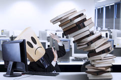 Businessman with cardboard head overworked. Businessman overworked with a pile of books in the office Stock Photography