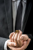 Businessman carefully holding a butterfly that has settled on hi Stock Photo