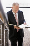 Businessman carefully reading paperworkon stairs Stock Photos