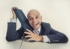 Businessman caressing on computer keyboard with funny face expression Royalty Free Stock Photos