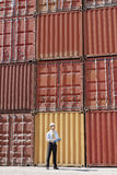Businessman with cargo containers. Portrait of mid adult businessman standing near cargo containers and holding clipboard. Vertical shape, full length stock images