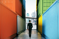 Businessman between cargo containers. Businessman walking towards city on concrete path between cargo containers. Success concept, 3D Rendering Stock Photography