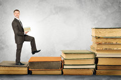 Businessman carries stack of books and walks up Royalty Free Stock Image