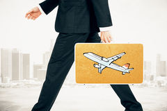 Businessman carries a suitcase with plane print at city backgrou Royalty Free Stock Photos