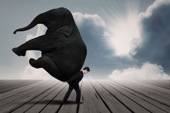 Businessman carry elephant by himself under blue sky. As leadership concept Royalty Free Stock Photography
