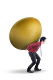 Businessman carry gold egg on white Stock Image