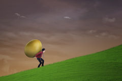 Businessman carry golden egg outdoor Stock Images