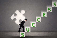 Businessman carry puzzle piece to gain success Royalty Free Stock Photography