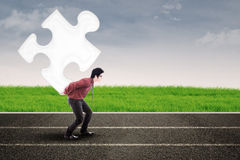 Businessman carry puzzle on road Royalty Free Stock Photo