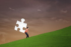 Businessman carry puzzle on steep hill Royalty Free Stock Photos