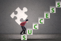 Businessman carry puzzle walking on success stairs Stock Photos