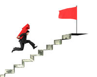 Businessman carrying arrow on money stairs to top red flag Royalty Free Stock Photos
