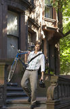 Businessman Carrying Bicycle While Descending Steps Royalty Free Stock Photos