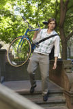 Businessman Carrying Bicycle While Descending Steps. Full length of young businessman carrying bicycle while descending steps Stock Image