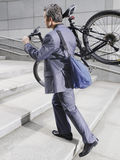 Businessman Carrying Bicycle Up Steps Stock Images