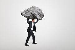 Businessman carrying big stone Royalty Free Stock Images