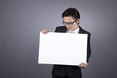 Businessman carrying a blank white board. Asian businessman looking down at a blank white board with copy space Stock Photos