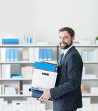 Businessman carrying a box and office folders Stock Photos
