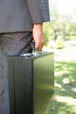 Businessman carrying briefcase outdoors Royalty Free Stock Photos
