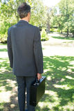 Businessman carrying briefcase in park Royalty Free Stock Photo