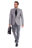 Businessman carrying briefcase and walking. On isolated white background Stock Photos