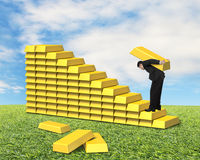 Businessman carrying bullion climbing on gold stairs Stock Photo