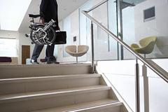 Businessman carrying commuter bicycle and briefcase up steps in lobby, low section, side view Royalty Free Stock Photo