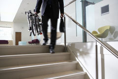 Businessman carrying commuter bicycle up steps in lobby, low section, rear view (blurred motion) Royalty Free Stock Photography