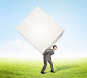Businessman carrying cube Royalty Free Stock Image
