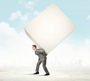 Businessman carrying cube Stock Images