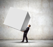 Businessman carrying cube Stock Photos