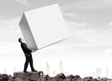 Businessman carrying cube Royalty Free Stock Images