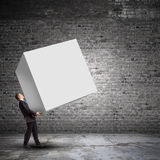 Businessman carrying cube Royalty Free Stock Photos