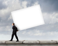 Businessman carrying cube Royalty Free Stock Photography