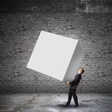 Businessman carrying cube Stock Photography
