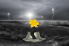 Businessman carrying 3D gold puzzle on money boat with storm. Businessman carrying 3D gold puzzle on money boat in sea with storm royalty free stock photography