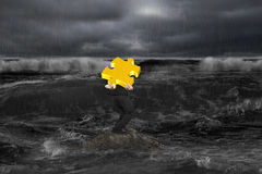 Businessman carrying 3D gold puzzle on rock in dark ocean. With on coming waves Stock Photos