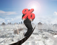 Businessman carrying 3D red percentage sign balancing on wire Stock Photos