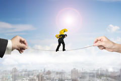 Businessman carrying dollar sign balancing tightrope with hands Royalty Free Stock Photography