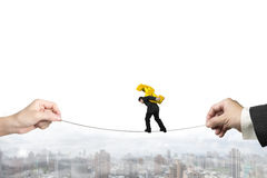 Businessman carrying dollar sign balancing tightrope with hands Royalty Free Stock Photo