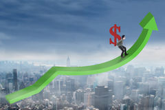 Businessman carrying dollar sign upward. Successful young businessman walking on the business graph while carrying dollar sign upward stock photo