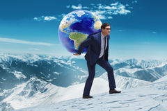 The businessman carrying earth on his shoulders Stock Photography