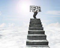 Businessman carrying fear concrete word on top of concrete stair Stock Images