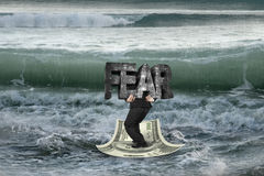 Businessman carrying FEAR on money boat in ocean with oncoming w Stock Photo