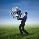 Businessman carrying a globe stock photo