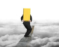 Businessman carrying gold bullion balancing on concrete ridge wi Royalty Free Stock Images