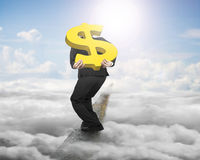 Businessman carrying gold dollar sign balancing on ridge with sk Stock Photo