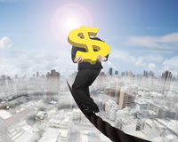 Businessman carrying gold dollar sign balancing on wire. Businessman carrying 3D gold dollar sign balancing on a wire, with sky sun mist cityscape background Royalty Free Stock Photo