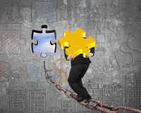 Businessman carrying gold jigsaw puzzle piece toward hole with s. Ky clouds view and business concept doodles wall background Stock Images