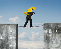 Businessman carrying golden dollar sign balancing on rusty chain Stock Photo